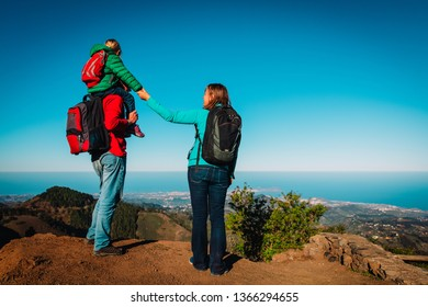 happy mom and dad with daughter travel in mountains