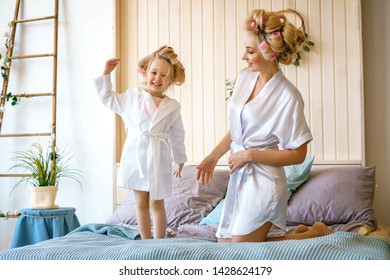 happy mom and daughter having fun on the bed in dressing gowns.