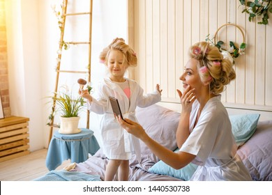 happy mom and daughter make a make-up sitting on the bed in the bedroom.