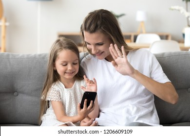 Happy mom and daughter make video call on smartphone talking with dad or relatives, smiling little girl and mother waving at cellphone, having skype conversation from home. Kids and technology concept