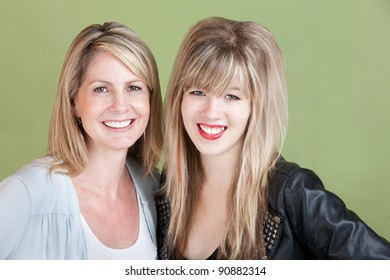 Happy mom and daughter smile over green background