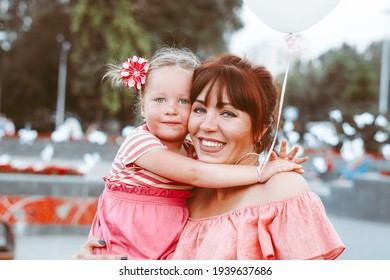 happy mom and daughter smiling at nature