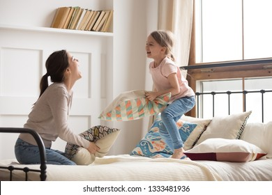 Happy mom elder sister and child girl enjoy funny pillow fight on bed, babysitter mother with little kid daughter having fun together in bedroom, cheerful family play laughing together in the morning