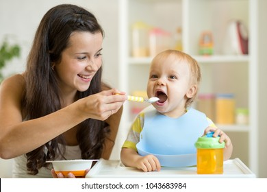 Happy mom feeding her baby son with spoon. Mother giving healthy food to her adorable child at home