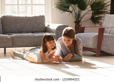 Happy mom helping child daughter drawing with colored pencils laying on warm floor together, smiling baby sitter mother teaching cute kid learning creative activity play laugh at home in living room
