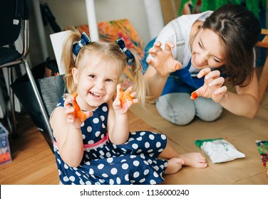 Happy mom and her child  playing with finger paint . Games with children with paint.Early  development.Spend  time with  kids.