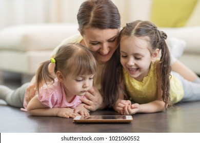 Happy mom and her children using digital tablet on floor at home