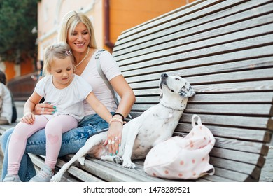 Happy mom and her daughter sitting on a bench with dog. Love of mother and daughter. Mothers day. Three girls together.
