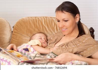 happy mom with her sleeping baby on sofa