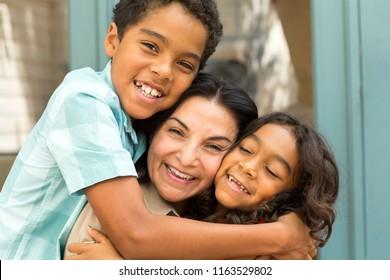 Happy mom hugging her children.
