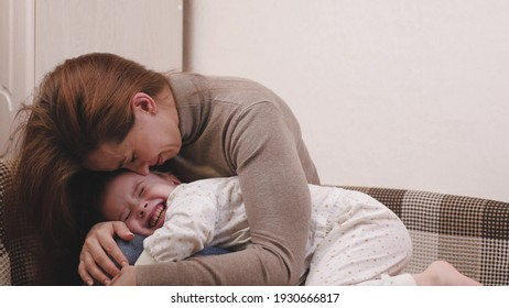 Happy mom hugs the baby while lying on the sofa in the children's room and smiles. Mother and daughter love in family relationships concept. Parental care and care of the kid. Your favorite baby will