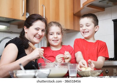 happy mom and kids in the kitchen making dough mixing flour, milk, eggs in a glass bowl