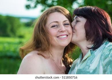 happy mom kisses daughter