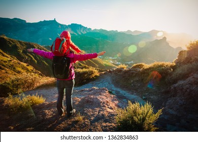 happy mom with little daughter enjoy travel in sunset mountains