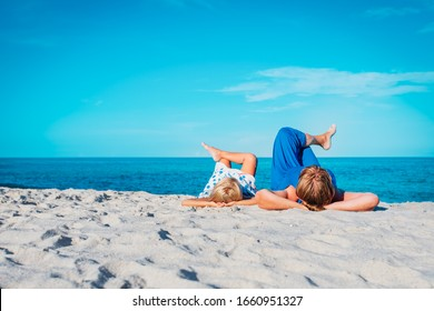 happy mom with little daughter relax on beach