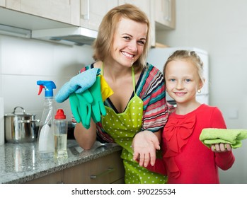 Happy mom and little girl cleaning at kitchen together