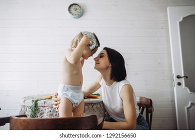Happy mom and little son have fun in the kitchen