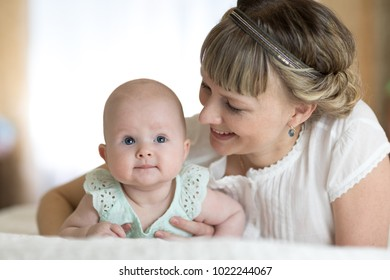 happy mom playing and hug with newborn baby in bed