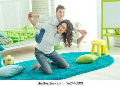 Happy mom plays with her son at home