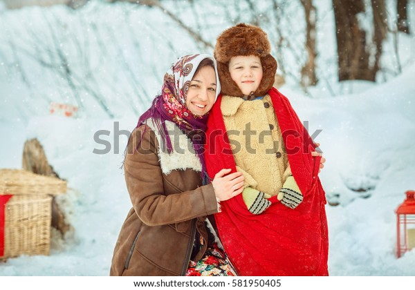 Happy mom and son hugs on the street in winter. Village style.. Retro National Russian flavor. Table decorated for the festivities. Pancake week. Feast of the end of winter
