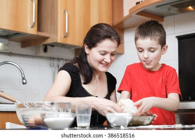 happy mom and son in the kitchen making dough mixing flour, milk, eggs in a glass bowl