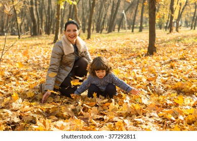 Happy mom and son playing in park with autumn leaves