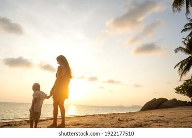 glückliche Mutter mit Sohn, der bei Sonnenuntergang am Strand spaziert