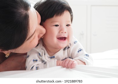 Happy moment of Asian mother playing and kissing her cute newborn baby at home Mother and child lifestyle with love and care concept