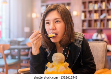 Happy moment with bingsu mango. Smiling asian woman eating Bingsu ( Korea food) mango served with sweetened condensed milk on table, Mango Bingsu Korea dessert poured mango sauce.