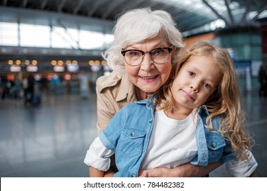 Happy moment. Portrait of charming positive gray-haired grandmother is hugging her pretty granddaughter from behind. They are looking at camera with joy while standing at airport hall. Copy space