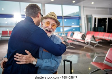 Happy moment. Portrait of pleased aged father in glasses and his grownup child are hugging each other while standing at airport lounge. Old man is looking at camera with glad. Copy space in right side