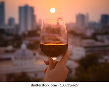 Happy moment of woman hand with red wine into glasses in a sunset background as on the rooftop at the bar restaurant