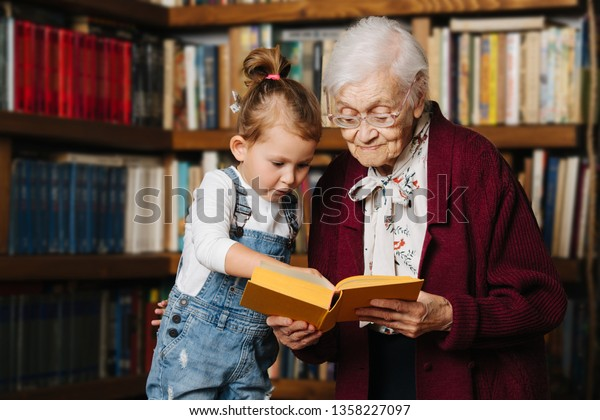 Happy moments with great grandma, senior lady spending quality time with her great granddaughter. Portrait in front of a bookshelf, holding one book in hands for the girl to read.