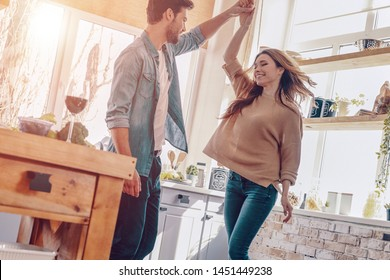 Happy moments together. Full length of beautiful young couple in casual clothing dancing and smiling while standing in the kitchen at home