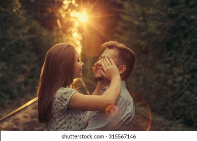 Happy moments of young couple at summer park alley in evening sunlight. Girl closing boy's eyes