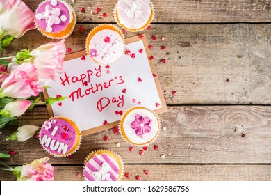Happy moms day greeting background. Mothers day sweet cupcakes, with gift boxes, coffee cappuccino cup, flowers. Wooden background copy space - Shutterstock ID 1629586756