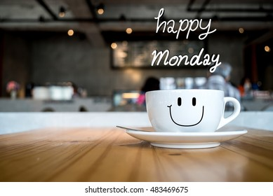 Happy Monday coffee cup on wooden background with smile face on cup., in coffee shop