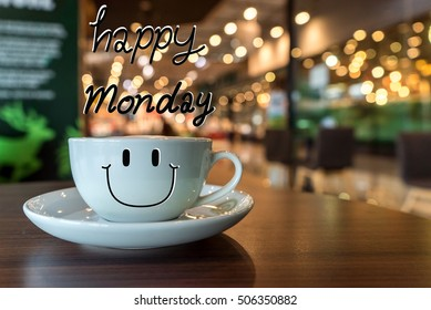 Happy Monday coffee cup on wooden background with smile face on cup, in coffee shop blur background