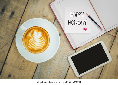 Happy Monday on paper with coffee cup on wood background