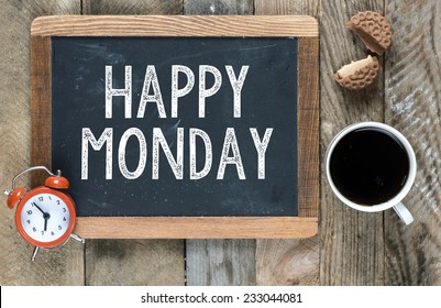 Happy monday sign on blackboard with cup of coffee ,cookie and clock on wooden background
