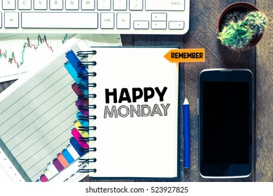 happy monday word written in the notebook on a wooden background.