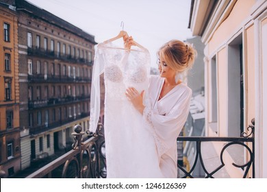 Happy morning of the bride. Girl admires her wedding dress
