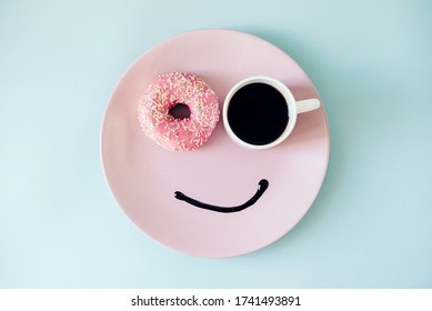 Happy morning! Donut and coffee on a plate. Funny face