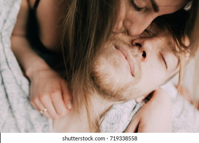 Happy morning of Young romantic couple in love have fun, kissing and hugs in bedroom . Love and relationships lifestyle, interior loft  bedroom.
