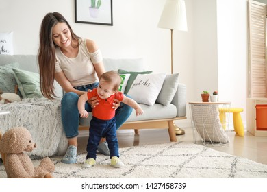 Happy mother with adorable baby boy at home