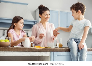 Happy mother. Attractive alert dark-haired young mother smiling and giving pills to her son sitting on the table and her daughter having breakfast
