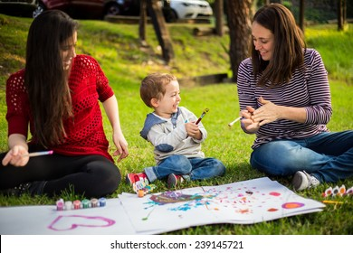 Happy Mother aunt sister and son child painting in the park.