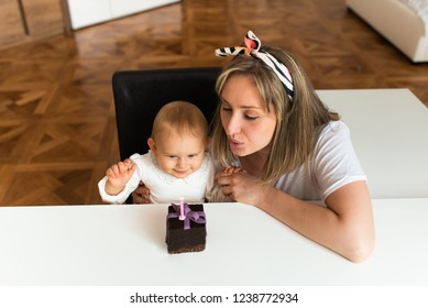Happy mother and baby blowing candles for baby's first birthday cake. Mommy and baby smiling together.