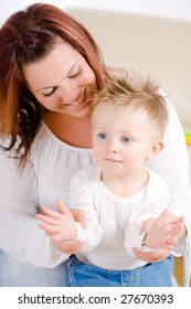 Happy mother and baby boy ( 2 years old ) clapping together at home, smiling.