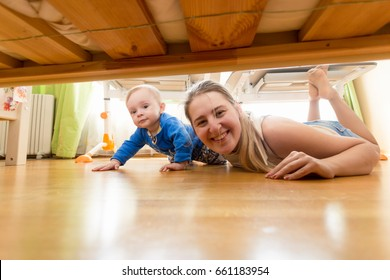 Happy mother and baby boy lying on floor and looking under the bed